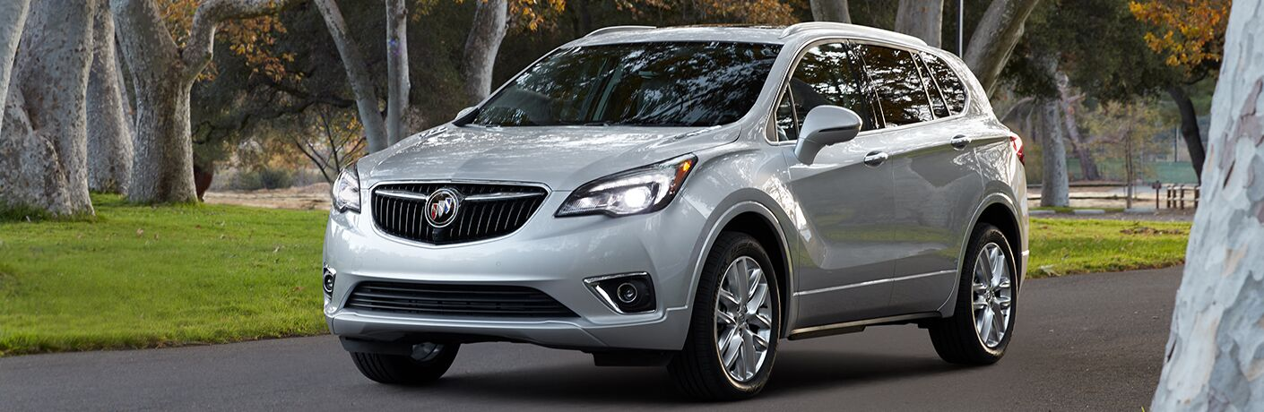 2019 Buick Envision exterior shot with gray silver paint color parked on an asphalt path within a forest park