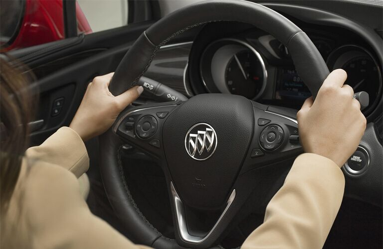 2019 Buick Envision interior closeup shot of driver's hands on the steering wheel with Buick badge