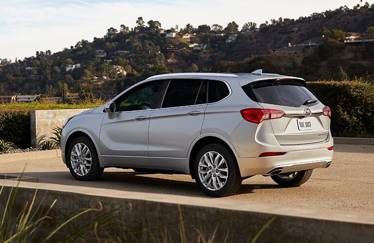 2019 Buick Envision exterior rear side shot with gray silver paint color parked on a concrete slab as the sun sets