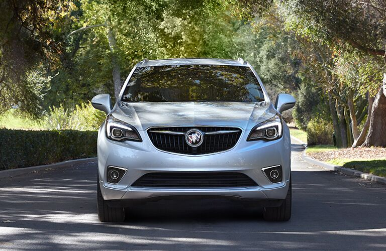 2019 Buick Envision exterior front shot showcasing grille, bumper, and headlights, parked on a road with trees and a short stone wall