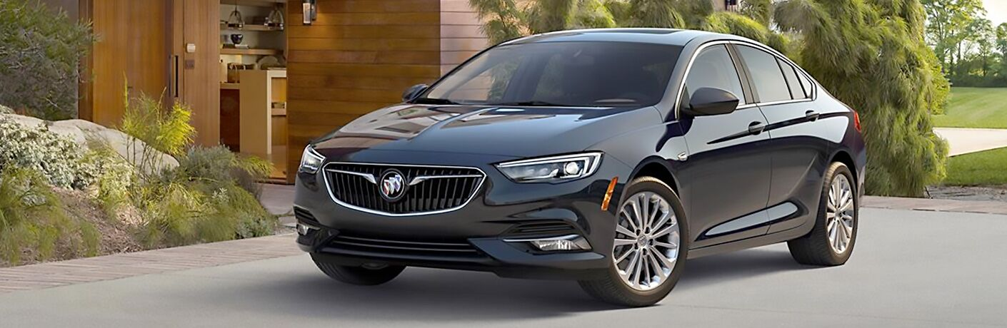 2019 Buick Regal Sportback exterior shot with black paint color parked on the driveway plaza of a fancy house