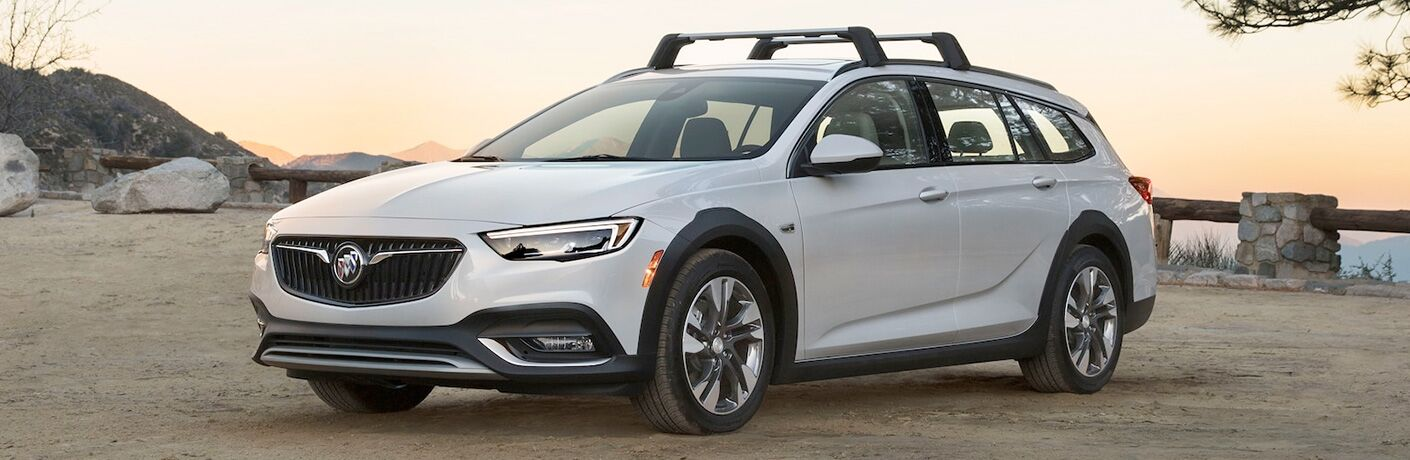 2019 Buick Regal TourX with white paint color and attached roof rails parked on a sandy beach at sunset