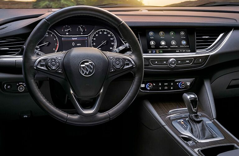 2019 Buick Regal TourX interior shot closeup of steering wheel, infotainment touchscreen, and transmission