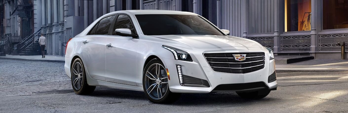 2019 Cadillac CTS exterior shot of white paint color parked on a stone tiled road with columned buildings