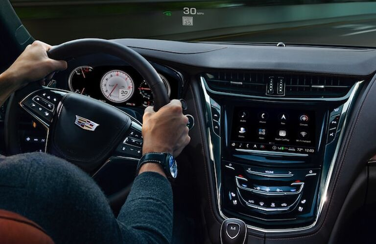 2019 Cadillac CTS interior shot of driver's hands on the steering wheel as infotainment display is lit up