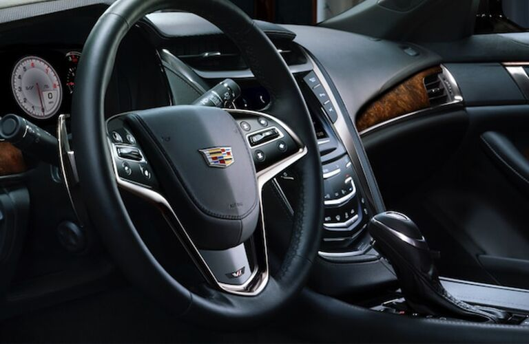2019 Cadillac CTS interior shot of steering wheel with Cadillac badge, transmission, and dashboard infotainment