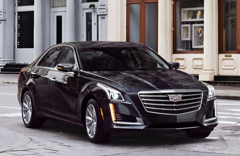 2019 Cadillac CTS exterior shot with black paint color parked on a road near old-fashioned shops