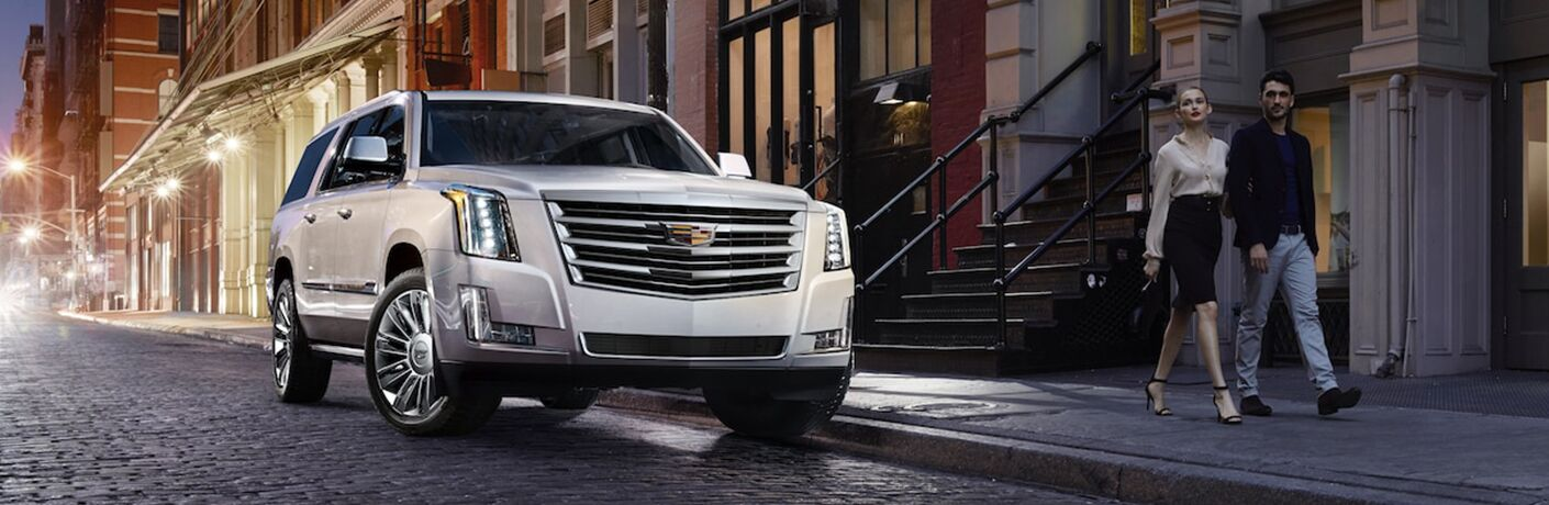 2019 Cadillac Escalade exterior shot with white paint color parked on a dark tiled road near old fashioned apartments during the nightlife of an urban city near a walking couple