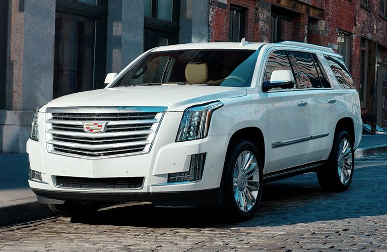 2019 Cadillac Escalade exterior shot with white paint color parked on a stone tiled road near brick buildings