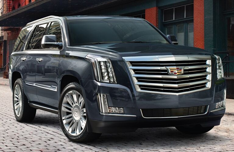 2019 Cadillac Escalade exterior front shot with dark blue metallic paint color parked on a stone tiled road