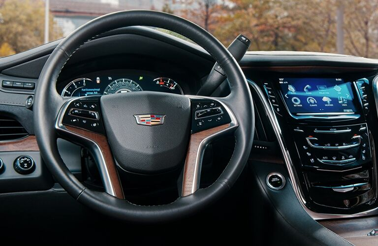 2019 Cadillac Escalade interior closeup shot of steering wheel with Cadillac logo badge, driver's display, and dashboard infotainment screen