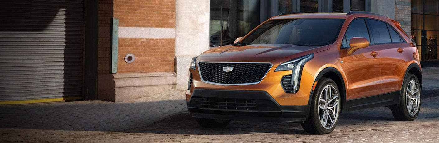 2019 Cadillac XT4 exterior shot with bronze orange paint color parked on a cobblestone path near a metal garage door