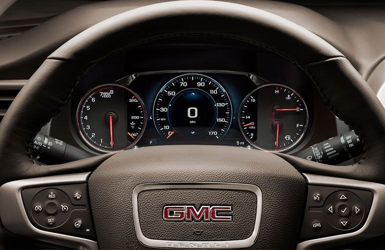 2019 GMC Acadia Denali exterior closeup shot of steering wheel branding and driver's display screen