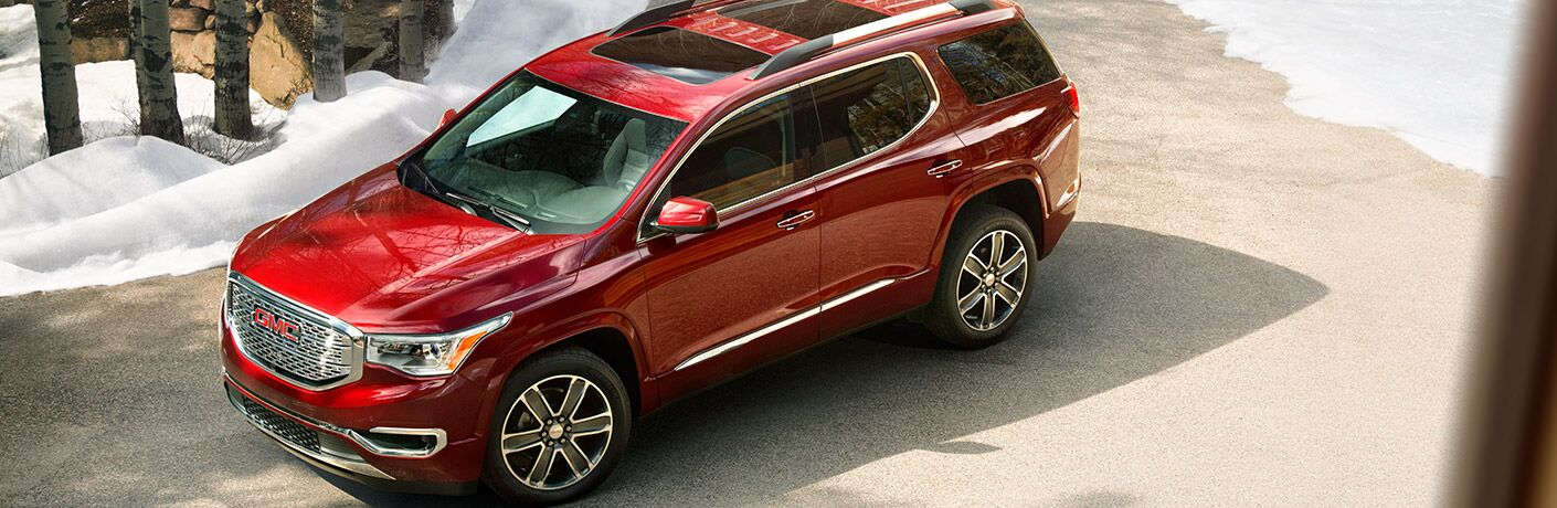 2019 GMC Acadia exterior overhead shot with red paint color parked near a snowy forest
