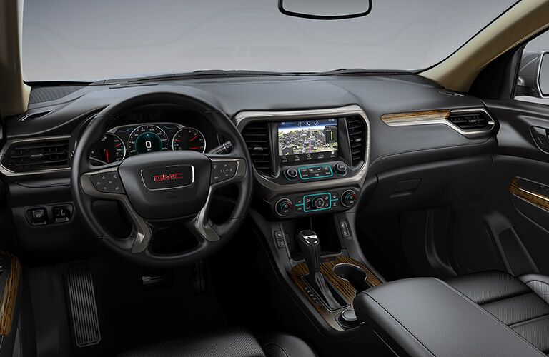 2019 GMC Acadia interior shot of front seating view of steering wheel, transmission, dashboard screen display, and accents