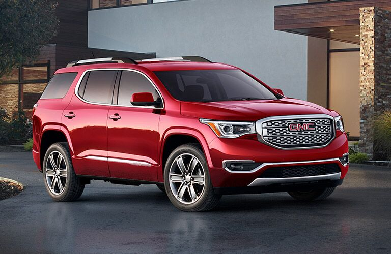 2019 GMC Acadia exterior shot with red paint color parked outside a modern fancy upscale house