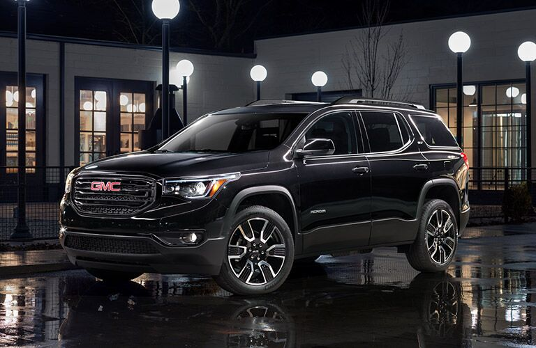 2019 GMC Acadia exterior side shot with black paint color parked near a building at night with streetlights on and rain puddles on the ground