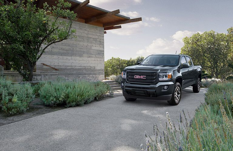 2019 GMC Canyon exterior shot with gray black paint color parked on an asphalt driveway outside of a house