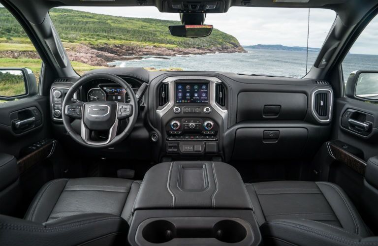 2019 GMC Sierra 1500 interior shot of front seating upholstery, steering wheel, and dashboard layout with green hills near the sea outside
