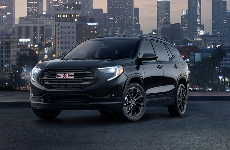 2019 GMC Terrain exterior shot black edition with LED headlights on with a city skyline at night in the background