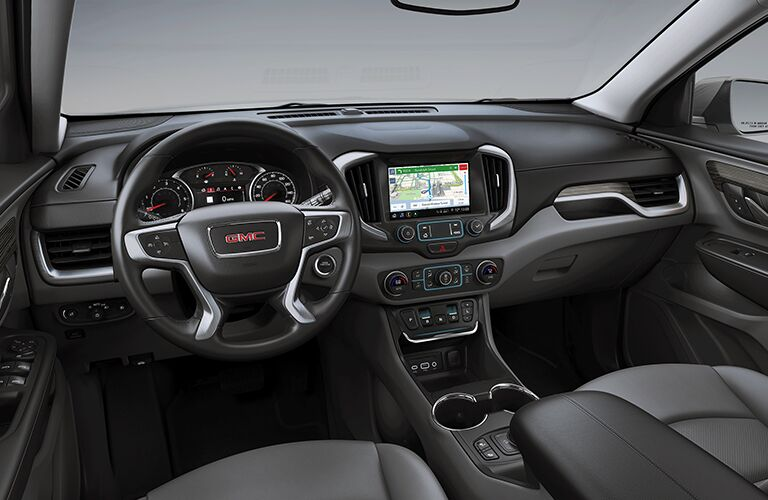 2019 GMC Terrain interior shot of front seating view of steering wheel, transmission, and dashboard display screens and technology