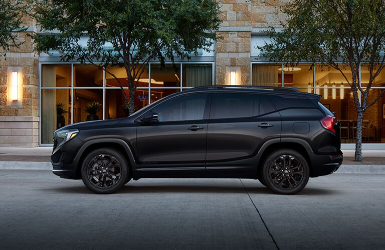 2019 GMC Terrain exterior side shot black edition parked on cement tiles in front of a glass paneled building