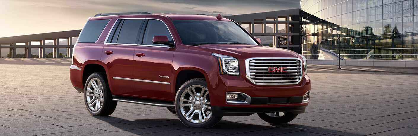 2019 GMC Yukon exterior side shot with red paint color parked on a stone tile plaza with a fancy glass building an a sunset behind it