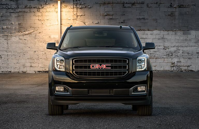 2019 GMC Yukon exterior front shot of headlights, grille, and front bumper with a brick wall background