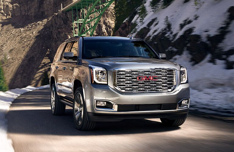 2019 GMC Yukon Denali exterior shot with dark silver paint color driving on a mountain highway