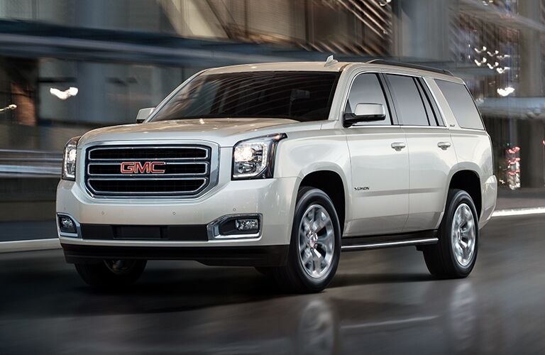 2019 GMC Yukon exterior shot with white paint color driving through a city at night