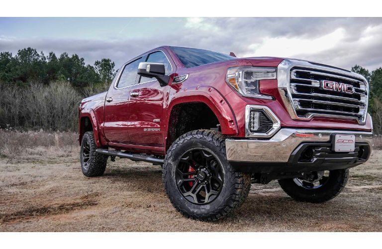2019 GMC Apex SCA performance truck exterior shot with red paint color parked on a sparse and dry grass plain near tall brush