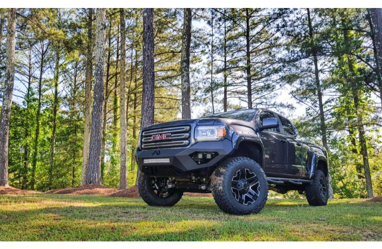 2019 GMC Canyon SCA performance truck exterior shot parked on grass in a forest surrounded by sparse green trees