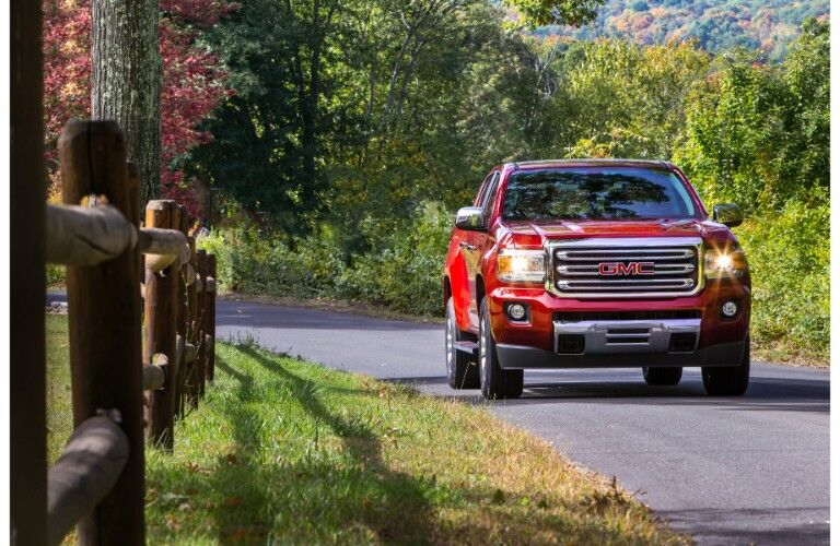 2019 GMC Canyon pickup truck exterior front shot driving through a lush country side near a wooden fence