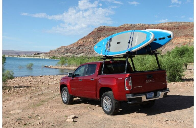 2019 GMC Canyon pickup truck exterior rear shot with red paint color parked on a dirt beach of cliffs near a lake of water