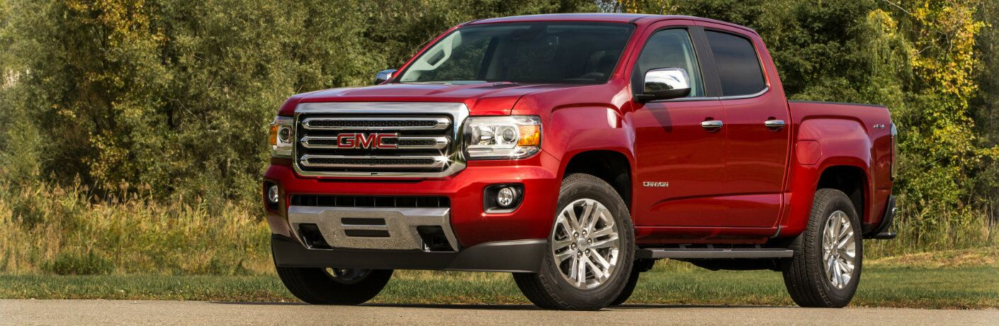 2019 GMC Canyon pickup truck exterior shot with dark red paint color parked on gravel in front of a forest of trees