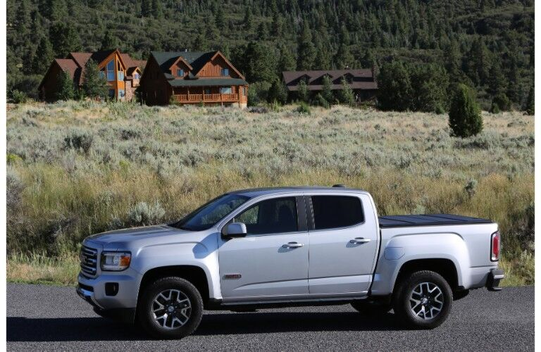 2019 GMC Canyon pickup truck exterior side shot with silver paint color parked in front of a tall green brush with a dark green forest of trees behind it