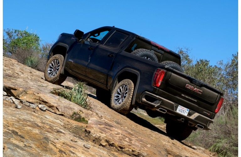 2019 GMC Sierra AT4 exterior rear shot driving up a stone hill with tires in its bed as dirt cakes on its wheels
