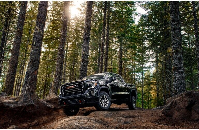 2019 GMC Sierra AT4 exterior shot parked on a bunch of stones as sun shines through the branches of tall and green trees