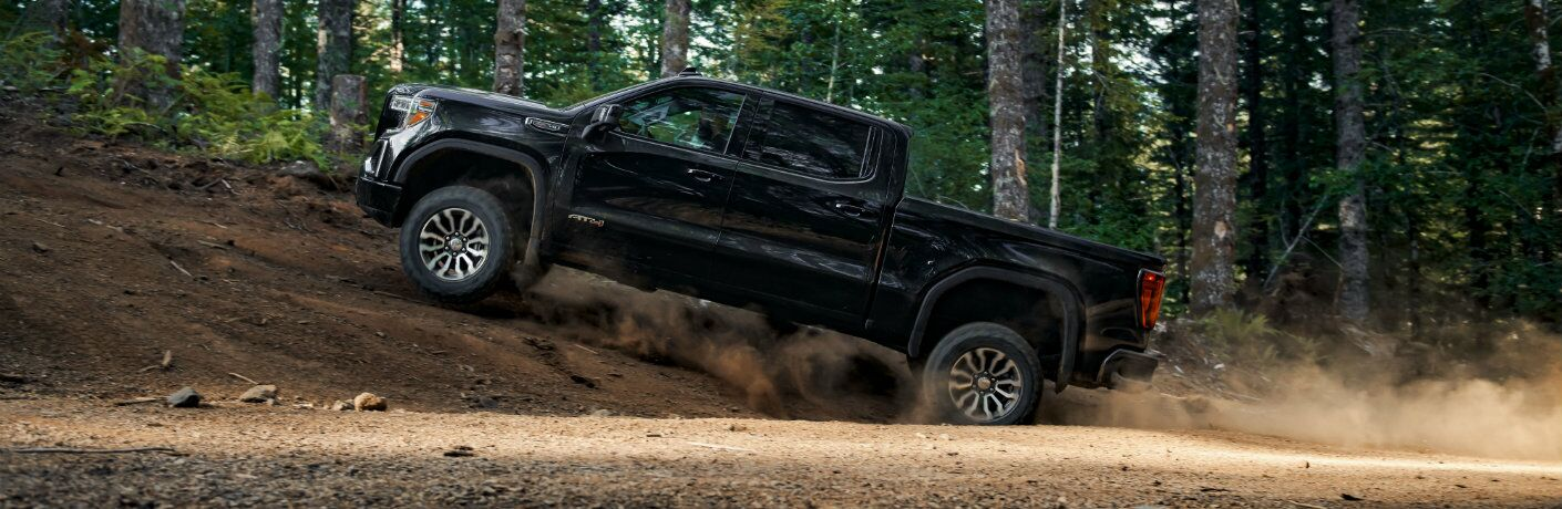 2019 GMC Sierra AT4 exterior side shot driving up a dirt hill within a forest of tall trees