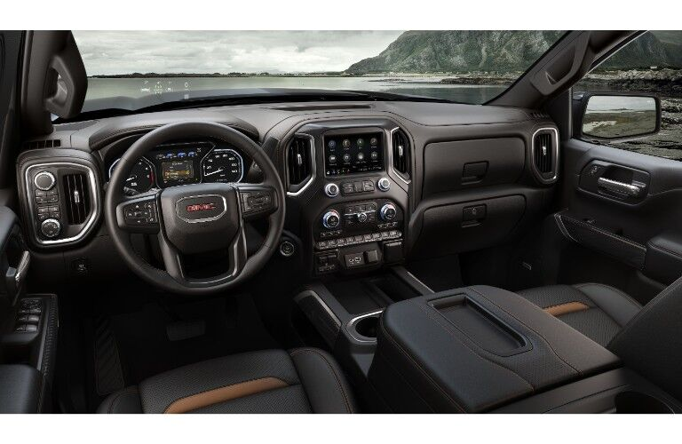 2019 GMC Sierra AT4 interior shot of front seating, dashboard layout and design, with a still and long lake seen through the windshield