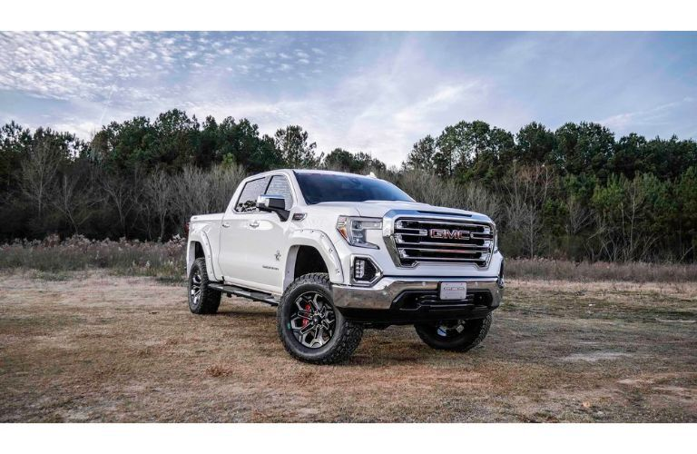 2019 GMC Sierra Black Widow with white paint job exterior shot parked on a dry grass field near fields of brush and a blue sky