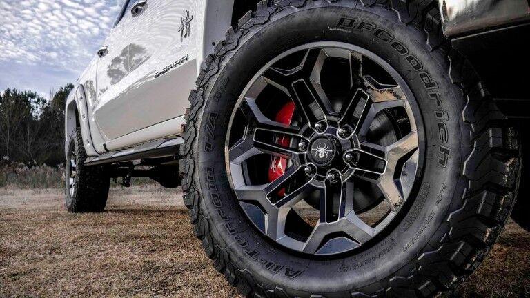 2019 SCA GMC Sierra Black Widow exterior closeup shot of unique tire and wheel design with Black Widow emblem badge