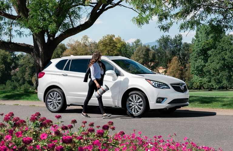 2020 Buick Envision exterior shot with white paint color parked in a park near a grass field and garden as its driver approaches