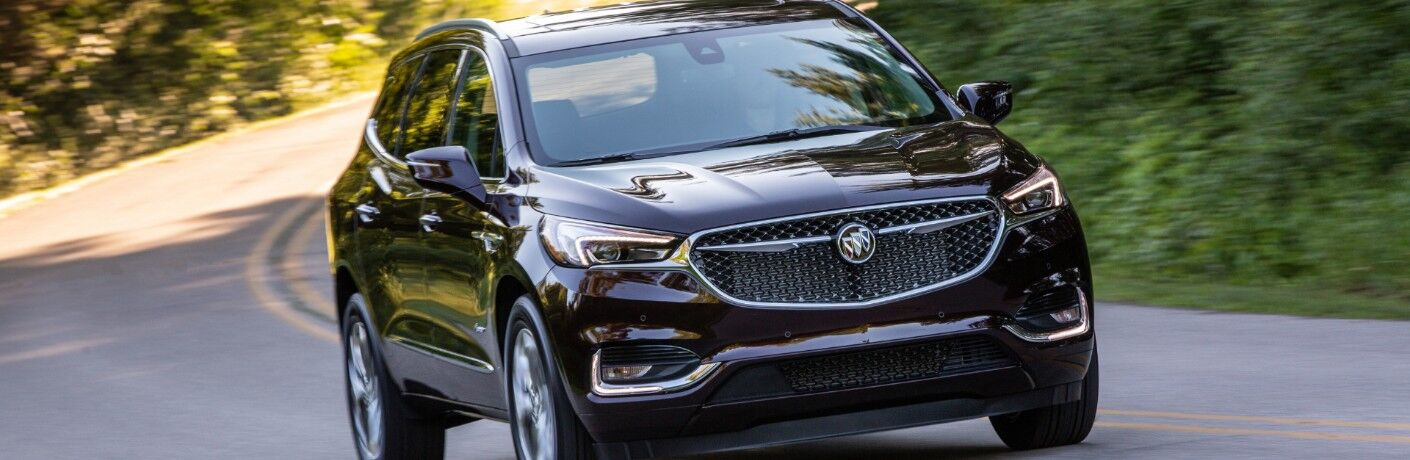 2020 Buick Enclave Avenir exterior front shot with dark red paint color driving on a forest highway road