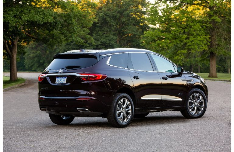 2020 Buick Enclave Avenir exterior rear shot with dark black paint color parked on a asphalt road surrounded by trees