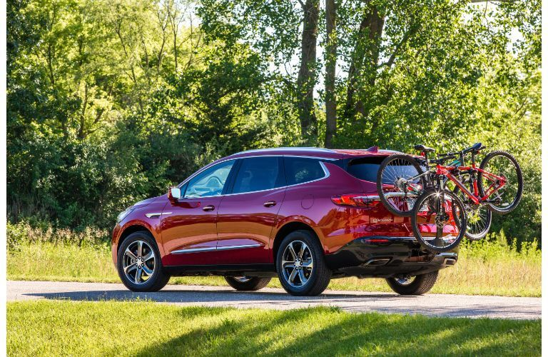 2020 Buick Enclave Sport Touring exterior side rear shot with red painr color surrounded by grass, bushes, and trees