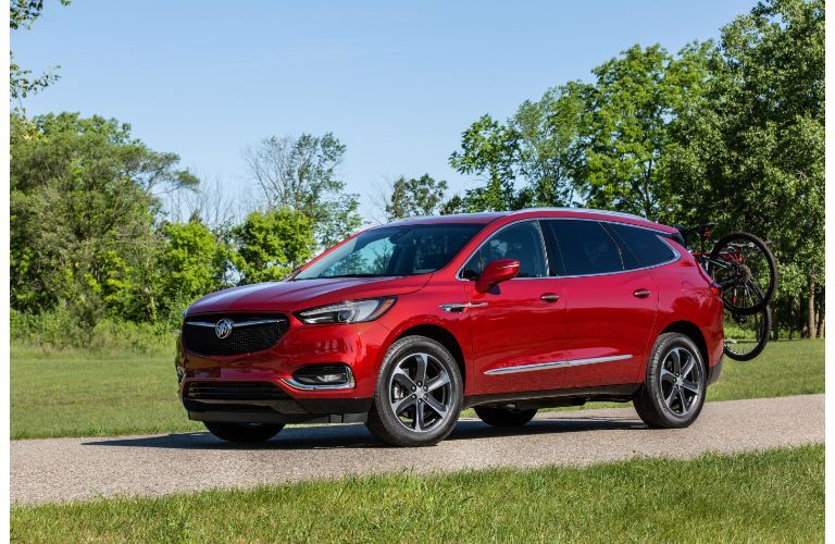 2020 Buick Enclave Sport Touring exterior side shot with red paint color parked in a green, forest wilderness