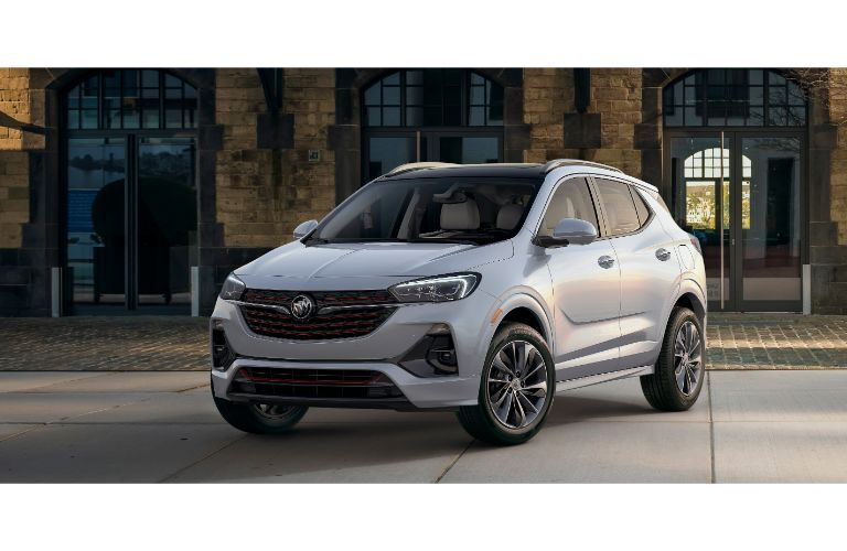 2020 Buick Encore GX exterior front shot with white gray paint color parked near a cobblestone path and brick building