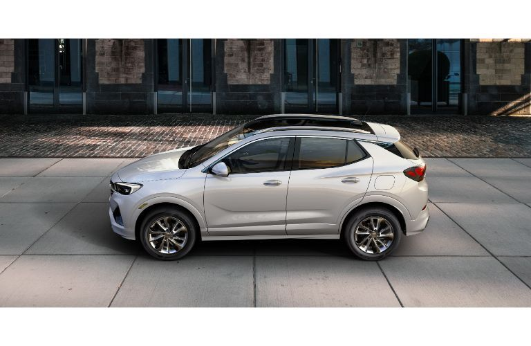 2020 Buick Encore GX exterior overhead side shot with gray silver white paint color parked outside a cobblestone path and brick building