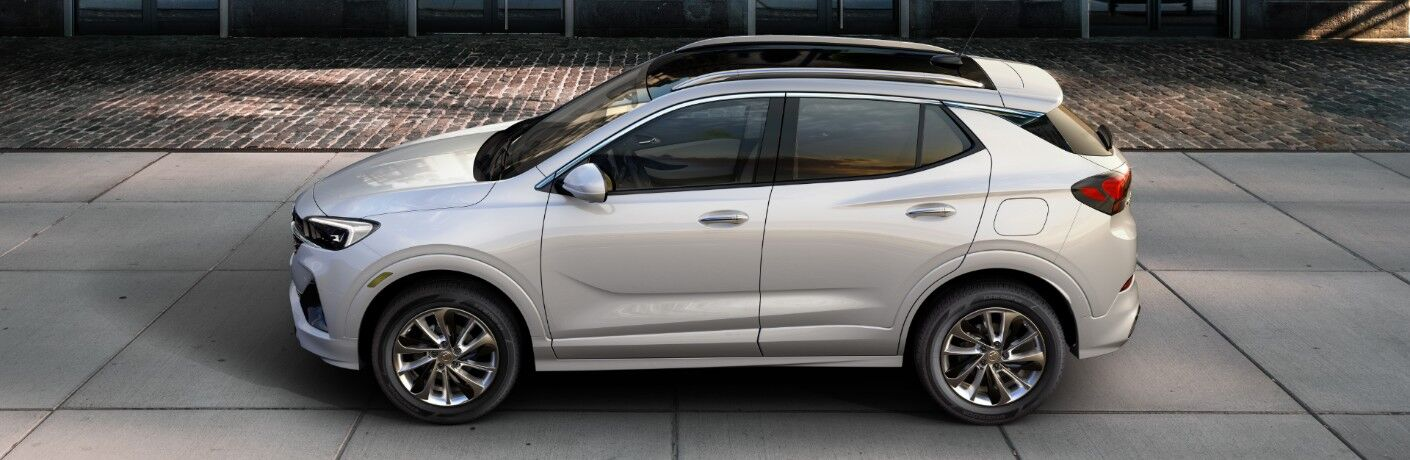 2020 Buick Encore GX exterior overhead side shot with gray white paint color parked in front of a building and cobblestone path